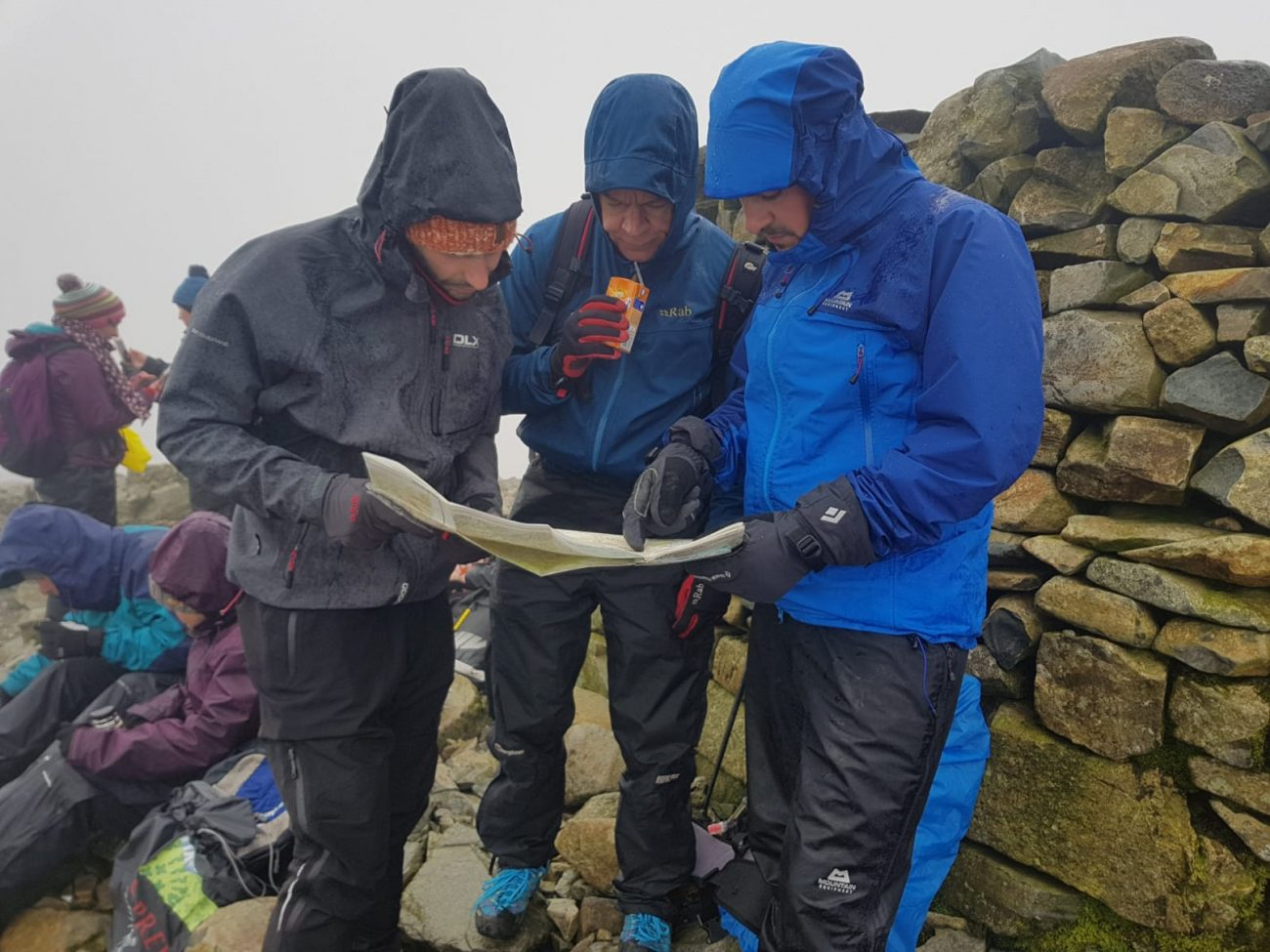 Photo of three men in waterproof gear for blog post about waterproofs